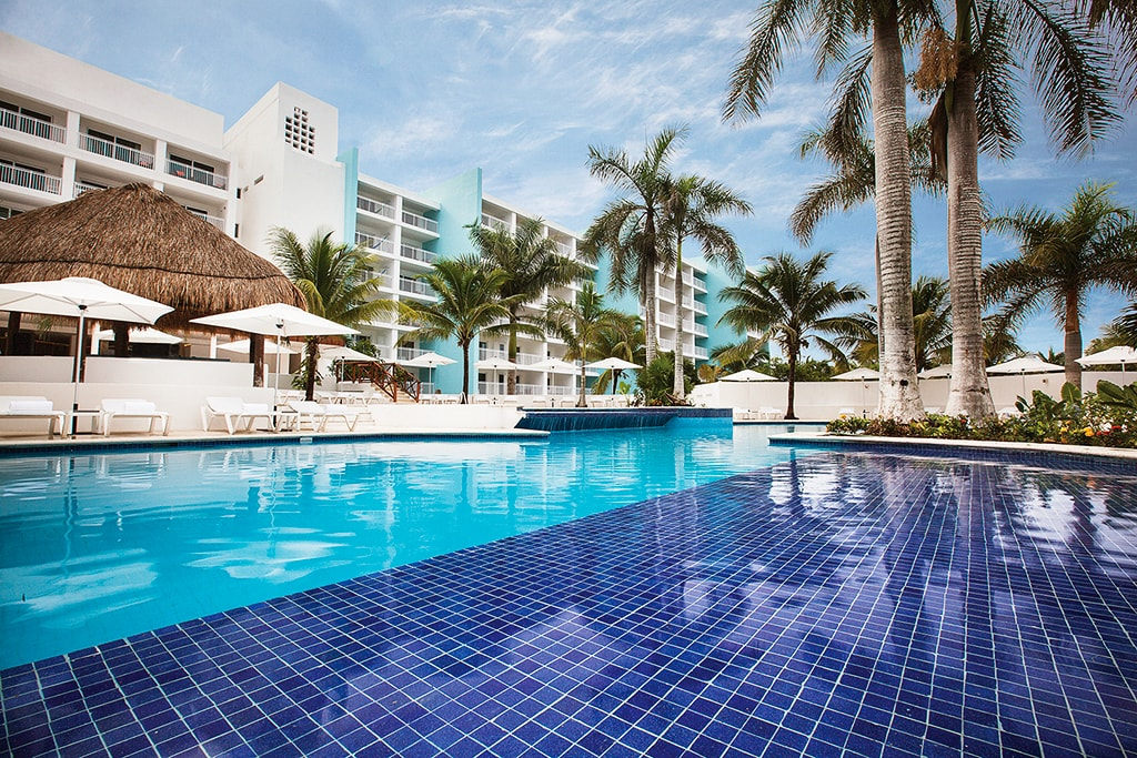 The pool is a focal point of daily social activities, with a swim-up bar and groups of lounges and day beds spaced around a landscaped deck.