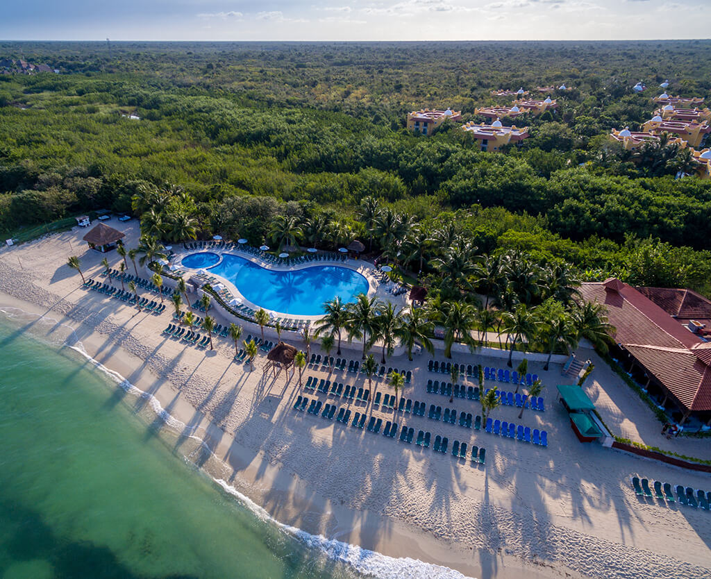An aerial view of Occidental Cozumel resort, showing the Beach Club and the guest rooms tucked into the surrounding jungle.