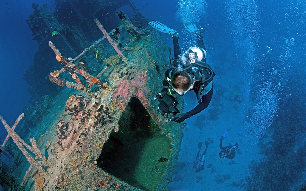 Divers explore the Marcha Fushi wreck, which is located in the waters of South Ari Atoll.
