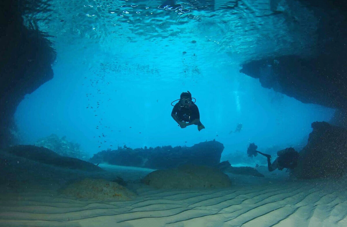 A diver enters the submerged cavern known as the Blue Room.