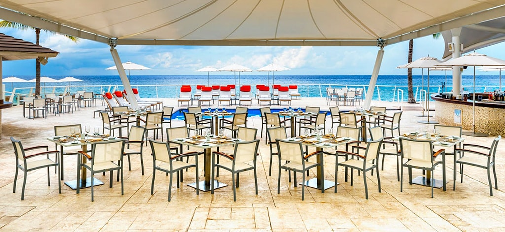 Tables at Flamingos sit under a large sun shade on the pool deck. It's a favorite for quick lunch bites and evening barbecues.