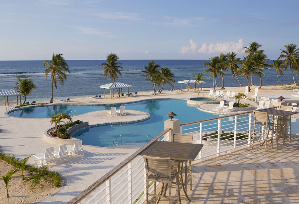 The second-story deck at Cayman Brac Beach Resort takes in views of pool and ocean.