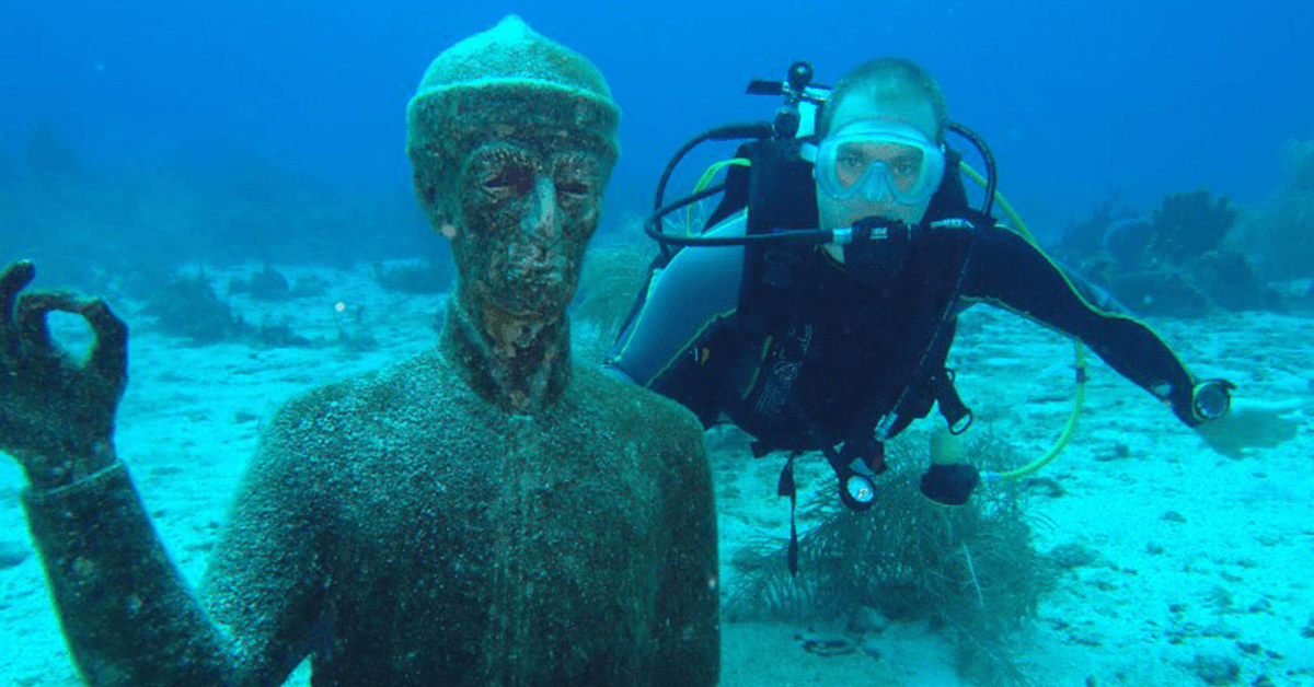 Diving in the Cousteau Marine Park is always a treat, here; this diver is taking the opportunity to be pictured with one of the Cousteau Underwater Statues in the reserve.