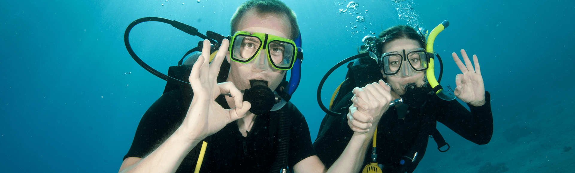 Couple giving scuba diving OK sign