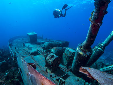 A scuba diver explores a ship wreck in the Bahamas