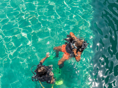 Scuba diver student learning in shallow crystal clear water
