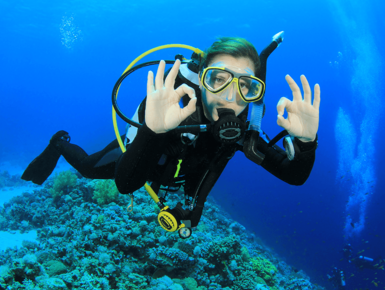 Young woman giving the Scuba Diver OK Sign